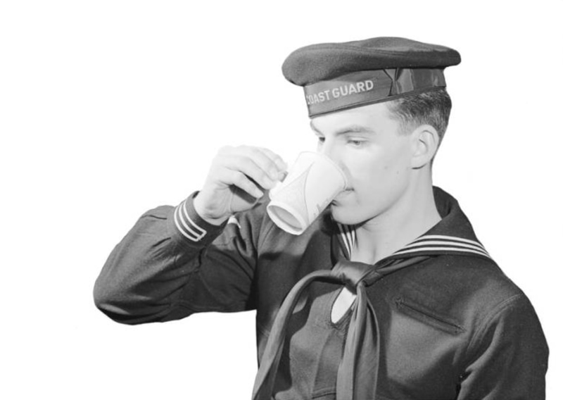 Member of U.S. Coast Guard in uniform and cap, drinking from paper cup with handle manufactured by Sutherland Paper Company.