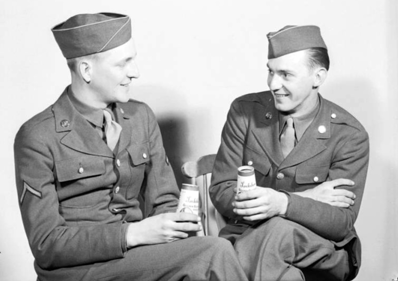 Two soldiers in uniform and caps, seated, drinking Lockshore brand milk from half-pint paper milk containers manufactured by Sutherland Paper Company.