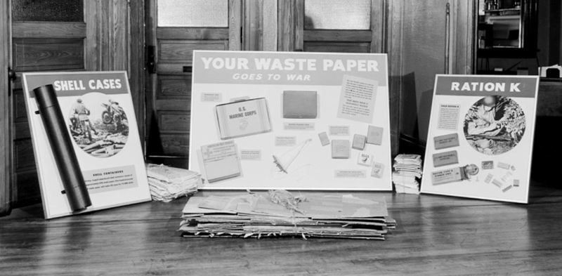 "Display boards ""Your Waste Paper Goes to War"" ""Ration K"" and ""Shell Cases"" feature types of packaging made from recycled waste paper, includes field ration boxes, cartons for dried eggs, and shell containers."