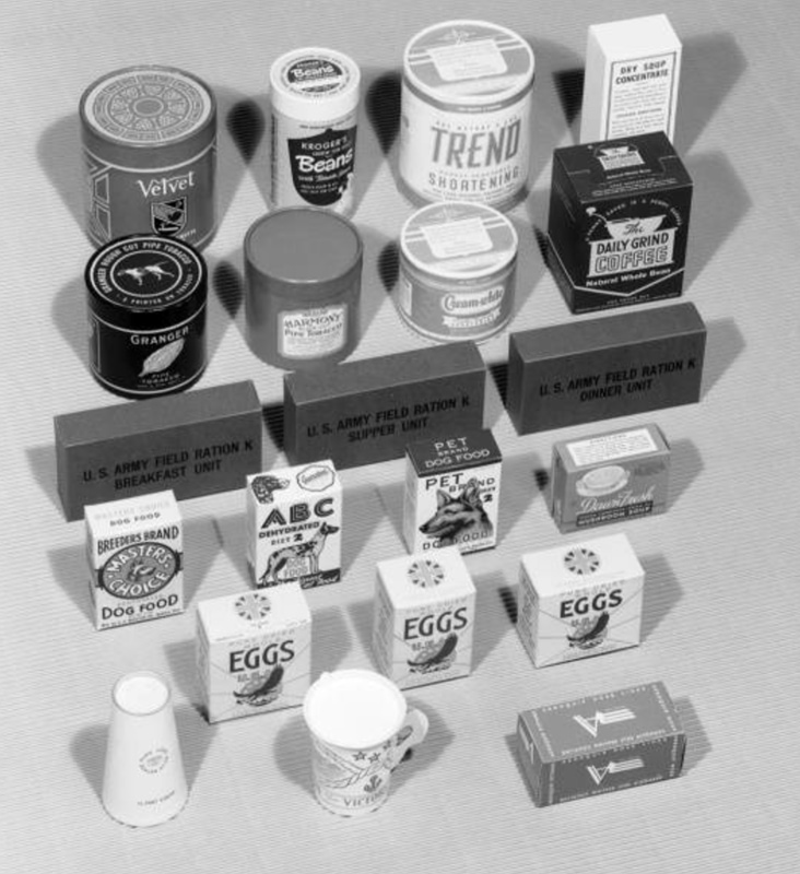 Paper carton display includes Velvet Tobacco, Kroger's Beans, Trend Shortening, Dry Soup Concentrate, Granger Fine Tobacco, Harmony Pipe Tobacco, Cream White Shortening, Daily Grind Coffee, U.S. Army Field Ration K, Breeder's Brand Dog Food, ABC Dehydrated Dog Food, Pet Brand Dog Food, Dawn Fresh Mushroom Soup, Eggs, and Aeroquip Hose Lines.