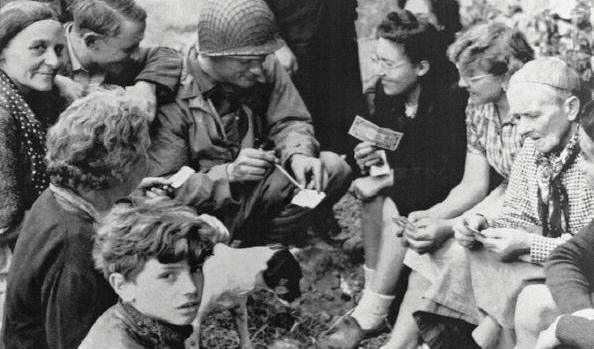 """Navy Beachmaster Joseph P. Vaghi explains the worth of invasion money on 19 June 1944 to villagers of St. Laurent sur mer, Normandy, France. In the early publication of this famous AP photo, military censors removed """"Navy Beachmaster"""" and used the words """"navy observer."""" – Nothing could be further from the truth!"""