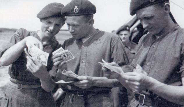 "Men of ""K"" Section, Signal Section, Headquarters 5th Parachute Brigade, discussing Invasion Currency at RAF Fairford on the 3rd June 1944. Signalman John Easby (left) parachuted into Normandy on the 6th June and later participated in the Rhine Crossing on the 24th March 1945, where he was taken prisoner. Signalman Douglas Davis (centre) was killed on the 6th June when the glider in which he was travelling crashed near Saint Vaast en Auge. Also killed in this crash were both of the glider pilots, Staff-Sergeant Colin Hopgood and Sergeant Daniel Phillips, Captain Spencer Daisley and Private John Aldred (both 13th Parachute Battalion). Copyright: Imperial War Museum."